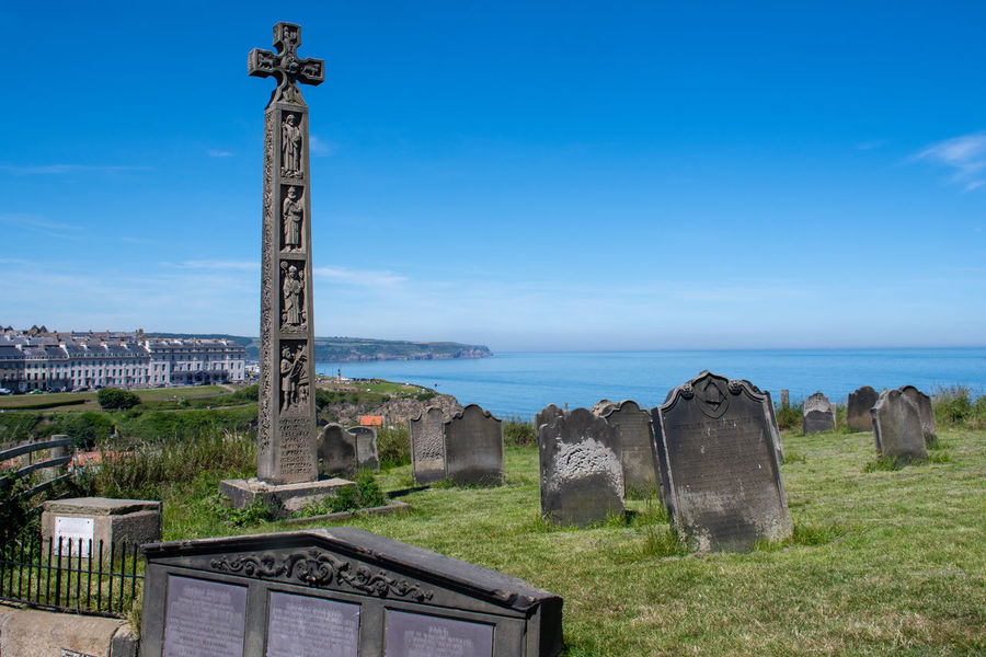 Graveyard overlooking sea at Whitby Cross Whitby Yorkshire Architecture Belief Cemetery Coast Coastal Coastal Feature Cross Grave Graveyard Outdoors Place Of Worship Religion Sky Symbol