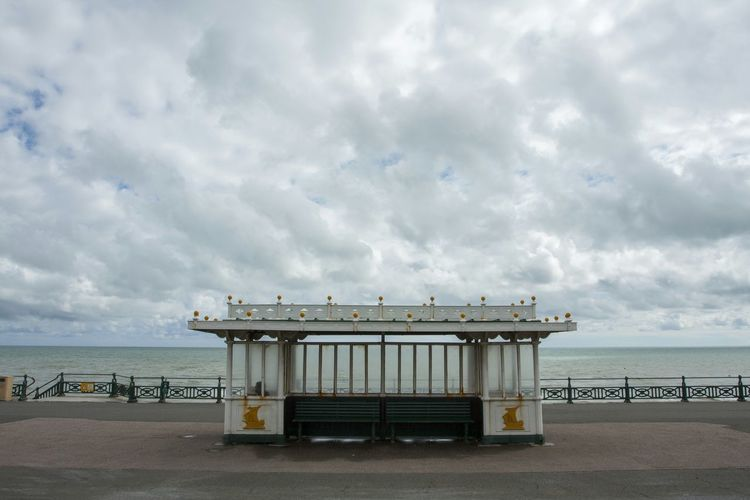 Built Structure By Sea Against Cloudy Sky