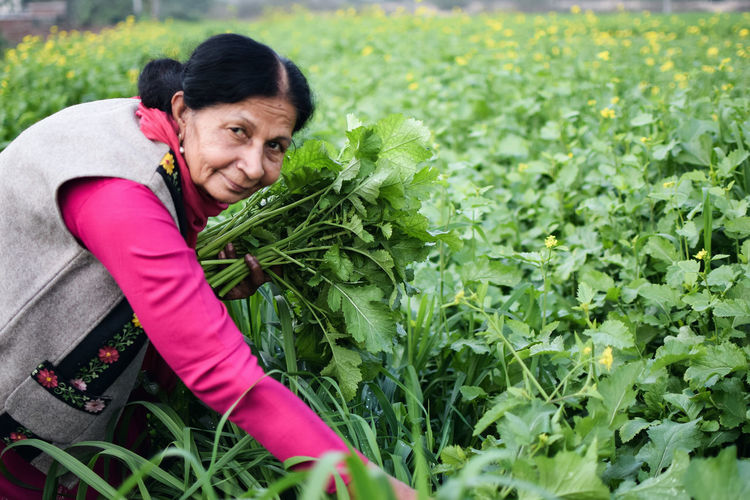 Portrait Of A Smiling Woman Picking Vegetables