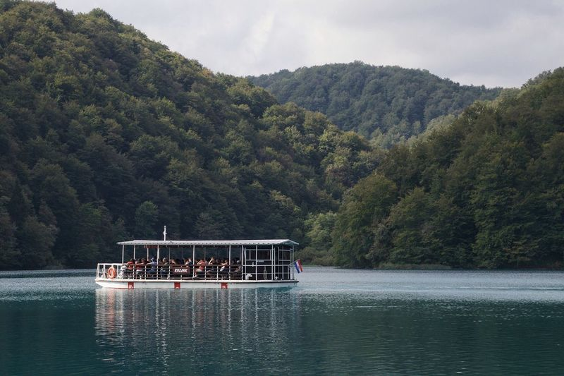 Plitvice boat Nautical Vessel Nature Mode Of Transport Transportation Tree Beauty In Nature Horizontal Croatia Plitvice National Park Water Surface Tranquil Scene National Park Scenics Water River Real People Sky Forest Day Outdoors Men Mountain Boathouse Togetherness People