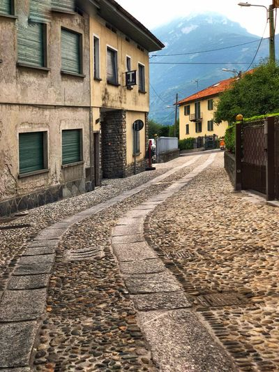 A small cobblestone street in an old Italian town with mountains in the background. Old Town Mountain City Town Old Built Structure Building Exterior Architecture Building The Way Forward Direction Residential District House Street City Cobblestone Footpath Road Window Sunlight Sky Day