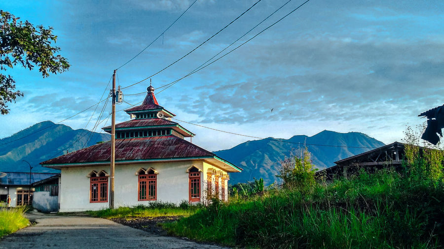 Traditional building on mountain against sky