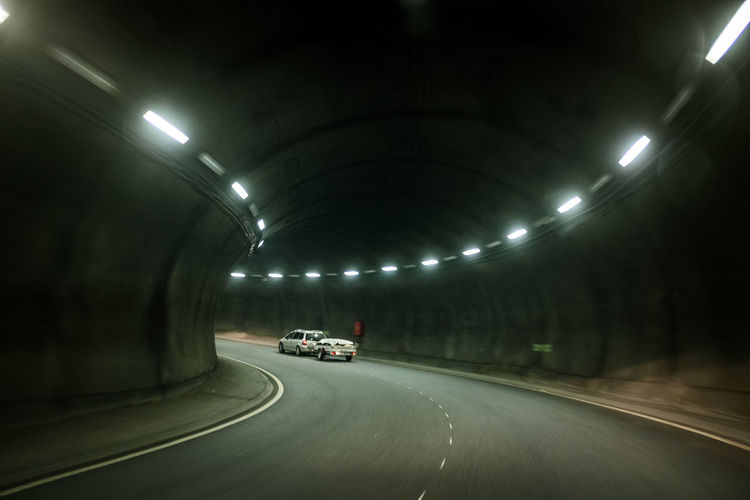 Cars moving on road in tunnel at night
