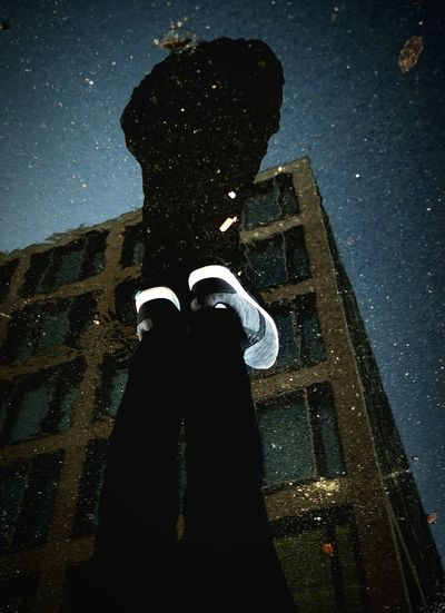 High angle view of man standing on puddle with reflection