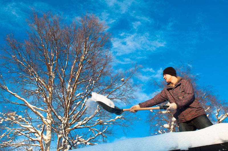 Adult Adults Only Bare Tree Beauty In Nature Blue Branch Cold Temperature Day Human Hand Low Angle View Mid Adult Nature One Person One Young Woman Only Only Women Outdoors People Roof Snow Cleaning Sky Tree Winter Women Young Adult