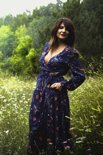 Young and attractive woman with a romantic dress in the woods Adult Beautiful Woman Beauty Fashion Field Grass Green Color Hairstyle Land Leisure Activity Lifestyles Nature One Person Outdoors Plant Real People Standing Three Quarter Length Women Young Adult Young Women