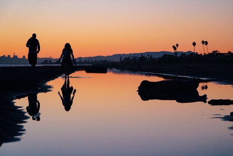 Silhouette men on lake against sky during sunset
