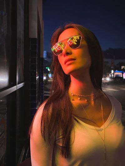 Close-up of beautiful woman wearing sunglasses standing outdoors at night