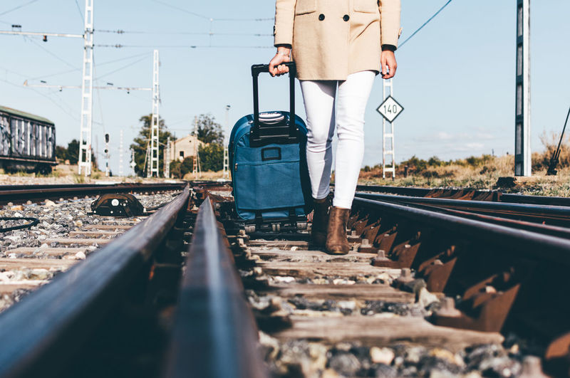 Woman dressed with a grey hat and beige jacket walking with her suitcase along a railway track.