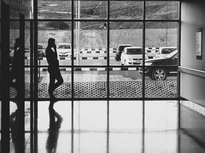 EyeEm Selects Walking Around Streetphotography WeekOnEyeEm darkness and light Blackandwhite Photography Light In The Darkness Transportation Light And Shadow Shadows & Lights Full Length Women Window Looking Through Window Snow Covered Transparent Transportation Building - Type Of Building Airport Departure Area Window Sill Passenger Boarding Bridge Airport Terminal Floating In Water Arrival Departure Board Wheeled Luggage