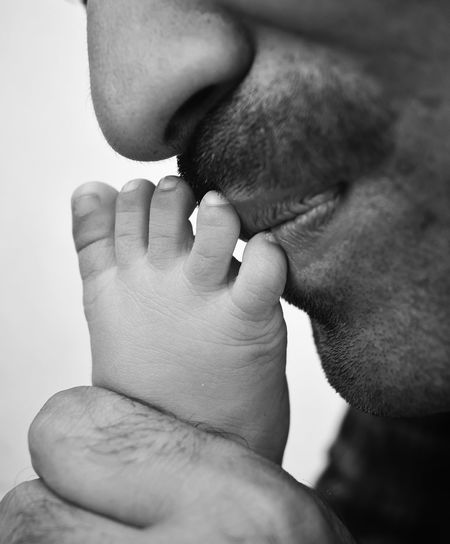 Father kissing leg of newborn baby. fatherhood moments, father's day.