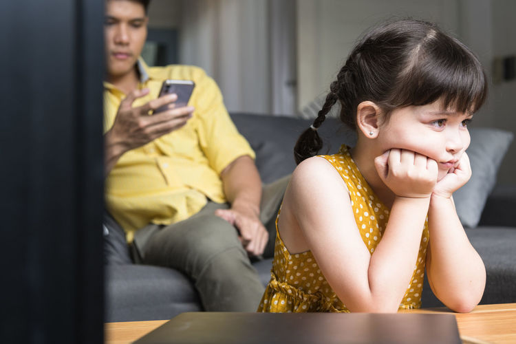 Angry girl sitting with father at home