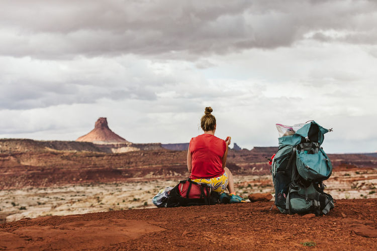 Rear view of women sitting on land against cloudy sky
