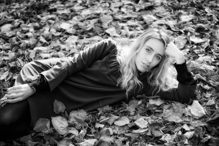 Portrait Of Smiling Young Woman Lying On Autumn Leaves At Park