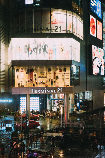 Reflection of illuminated building on glass window at night