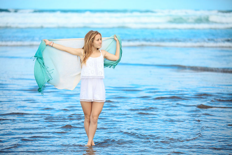 Woman Holding Shawl While Standing On Shore At Beach
