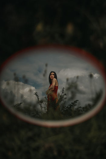 Young woman with reflection in water