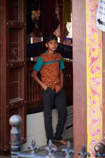A Small Kid Candid while he stands at the entrance of a temple. Pune, India. Looking At Camera Portrait Full Length Adults Only Happiness People One Person Indoors  Smiling Adult Young Adult Only Men One Man Only Day What Who Where
