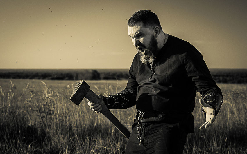 Angry hunter holding axe on grassy field against sky