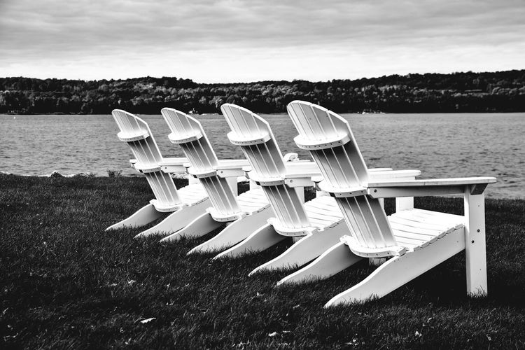 Chairs on grassy field by lake