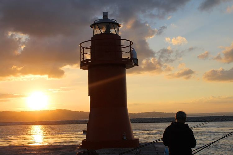 Silhouette man standing lighthouse at sea shore against cloudy sky during sunset