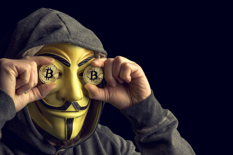 Man wearing mask holding bitcoins against black background