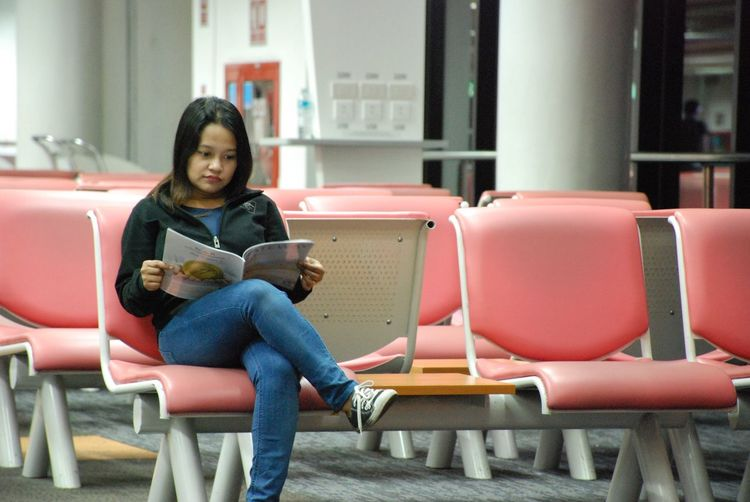 Young Woman Reading Magazine On Chair At Airport