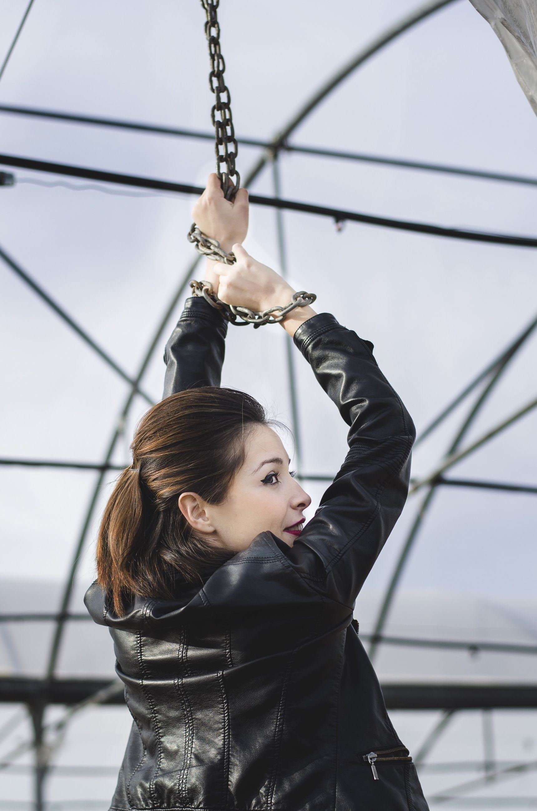 low angle view, lifestyles, leisure activity, holding, focus on foreground, casual clothing, day, metal, hanging, standing, outdoors, men, three quarter length, rope, arts culture and entertainment, front view, amusement park, sky