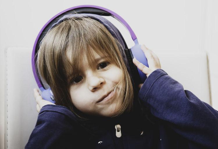 Close-up portrait of cute girl listening music through headphones