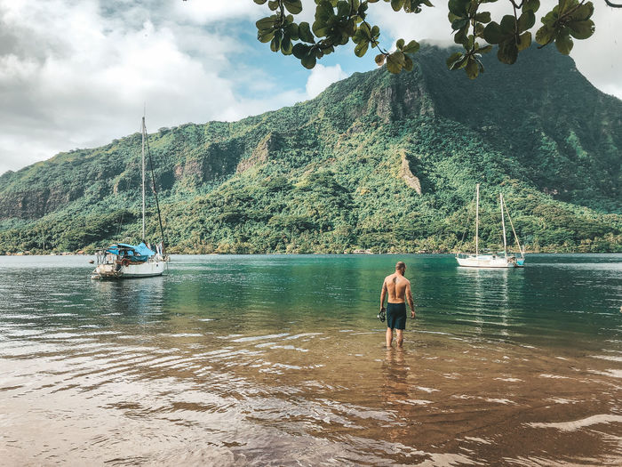 Rear view of shirtless man standing in sea