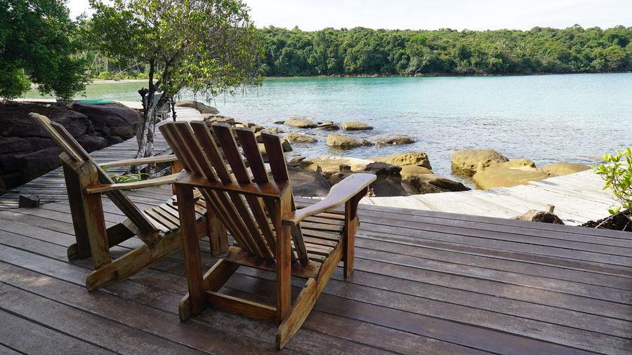 Adirondack chairs on floorboard against sea