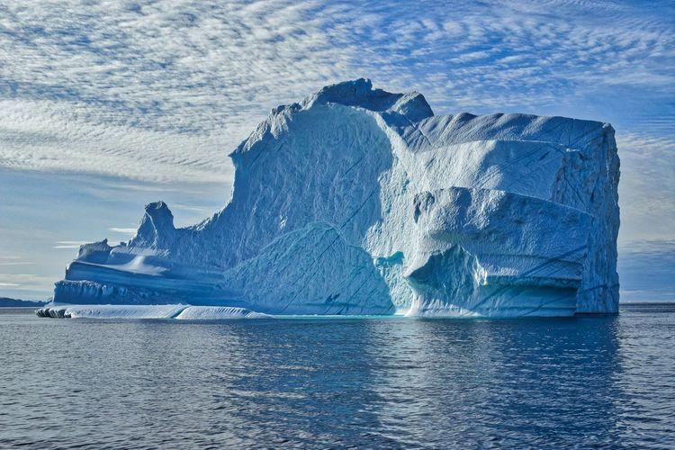 Frozen rock formation in sea against sky