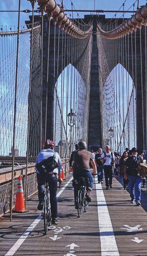 Low angle view of people walking on footbridge