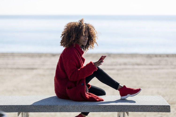 Woman using phone while sitting on bench at beach