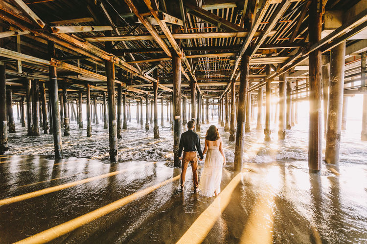 Rear View Of Couple Standing Under Santa Monica Pier