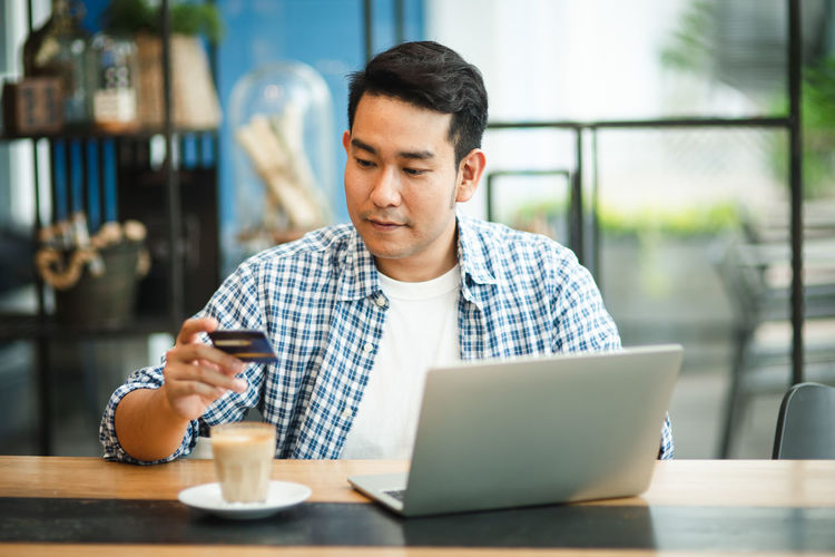 Man using phone while sitting on table at cafe
