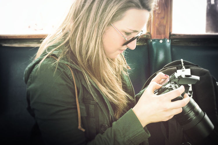 Side view of woman holding digital camera