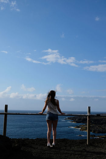 Rear view of woman standing by railing against sea and sky