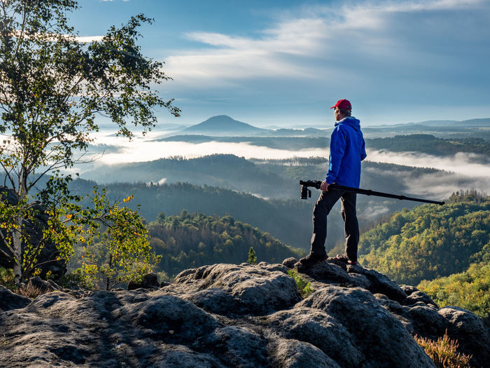 Photographer on cliff carry tripod. blogger hold tripod with camera. man at sunrise at open view