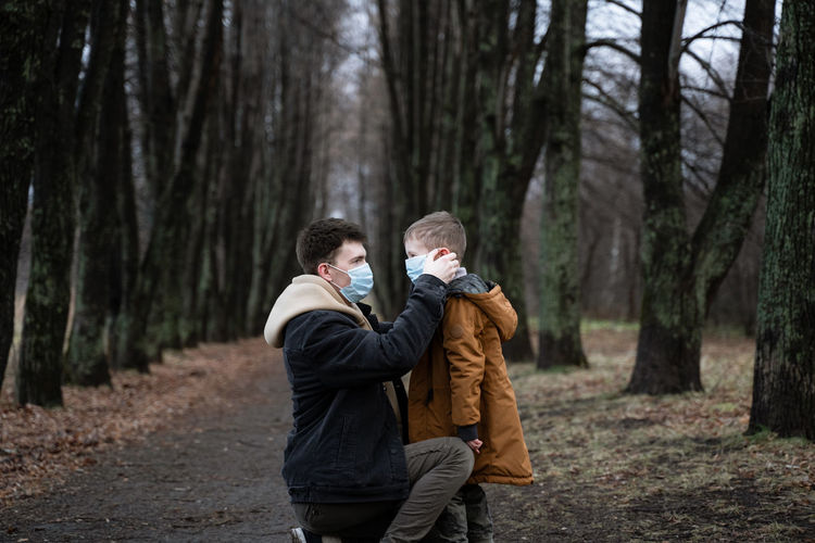 Father wearing mask to son in forest