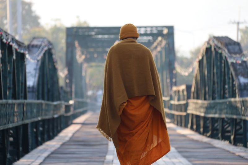 Rear view of monk walking on footbridge