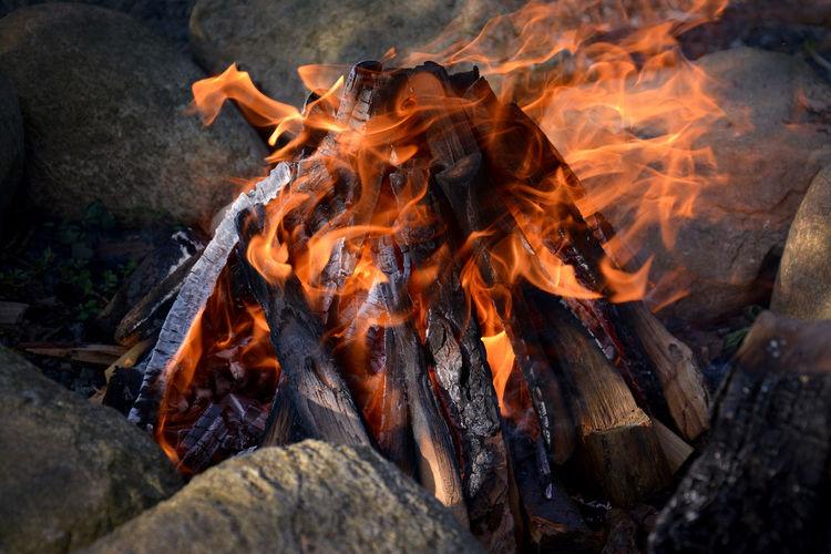 Close-up of bonfire amidst rock