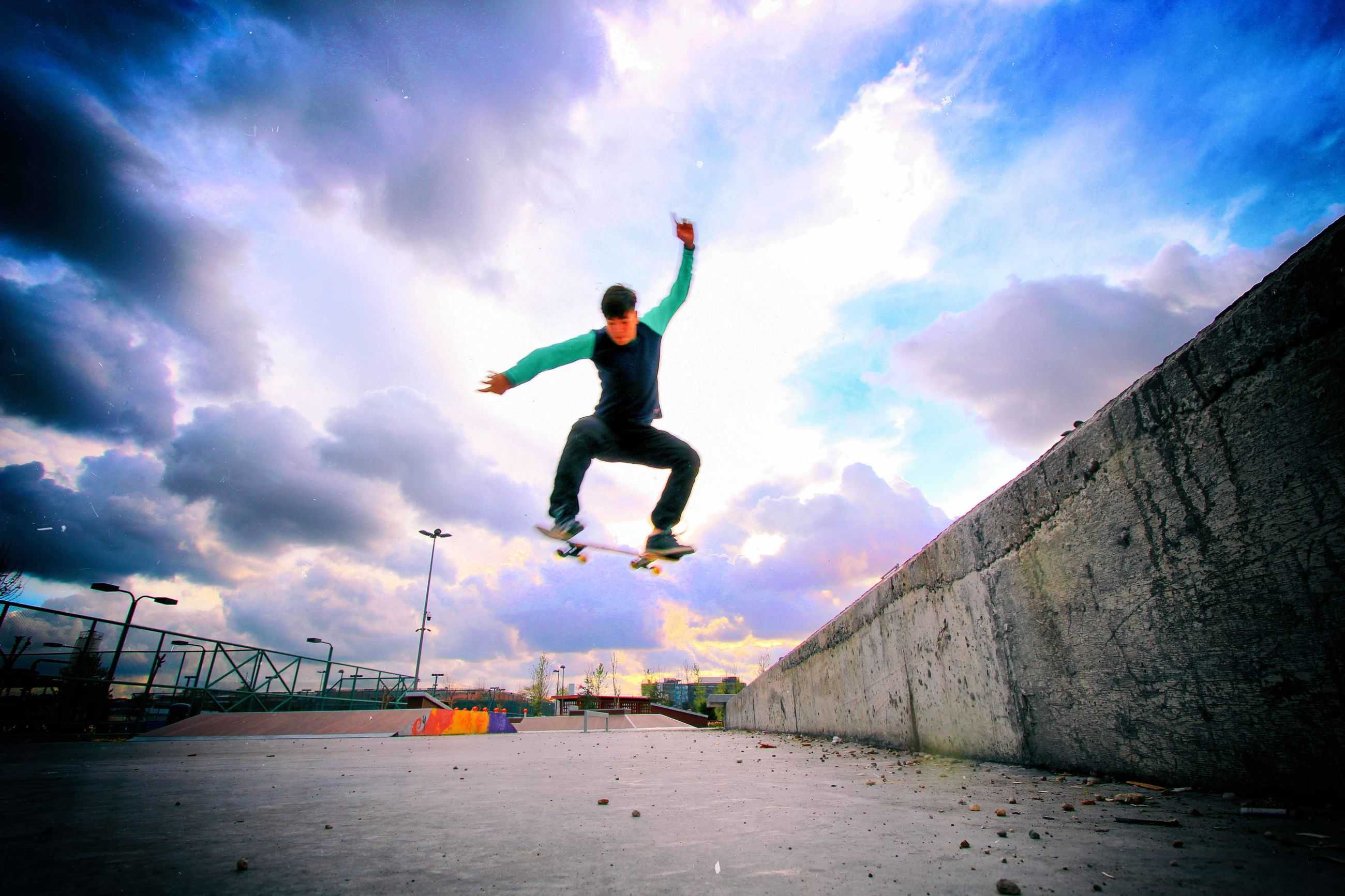 jumping, full length, mid-air, sky, skill, skateboard, cloud - sky, outdoors, stunt, one person, day, energetic, motion, men, extreme sports, real people, people