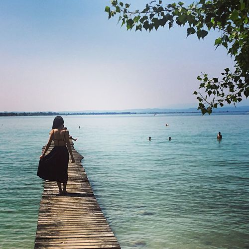 Quadriveri PeschieraDelGarda Verona Rear View Sea Water Real People Leisure Activity Beauty In Nature Nature One Person Women Lifestyles Clear Sky Weekend Activities Scenics Full Length Tranquil Scene Outdoors Day Relaxation Tranquility Standing Fashion Stories