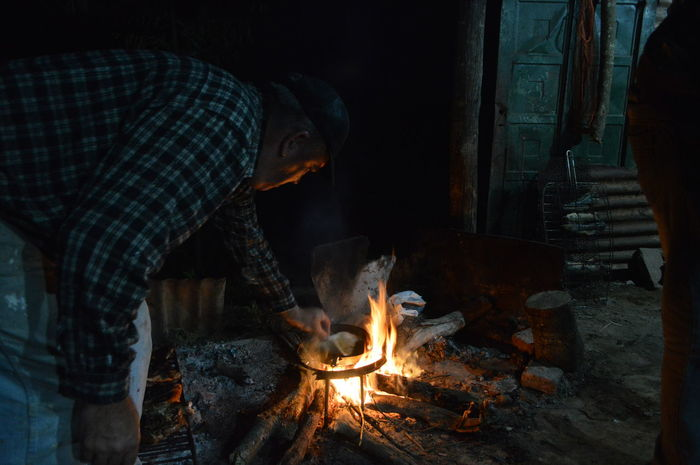 Cooking fried flour cakes - Ruso Burning Fire - Natural Phenomenon Fire Heat - Temperature Men Flame One Person Real People Wood - Material Wood Log Nature Standing Firewood Lifestyles Preparation  Food Adult Bonfire Preparing Food Campfire Outdoors