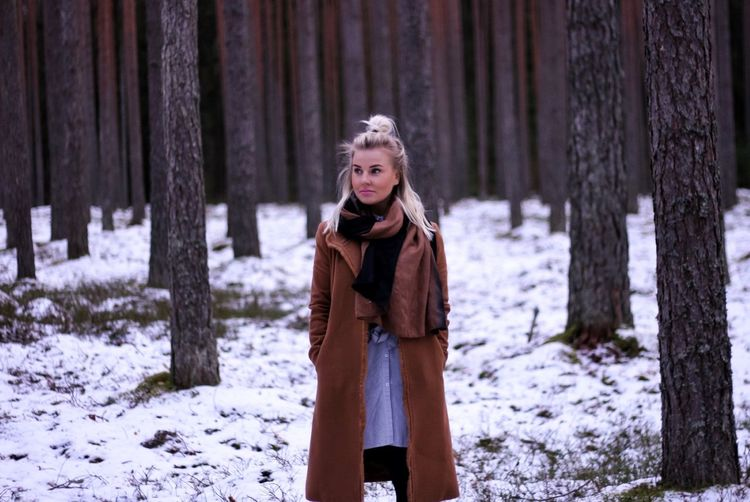 Young Woman Standing In Forest During Winter