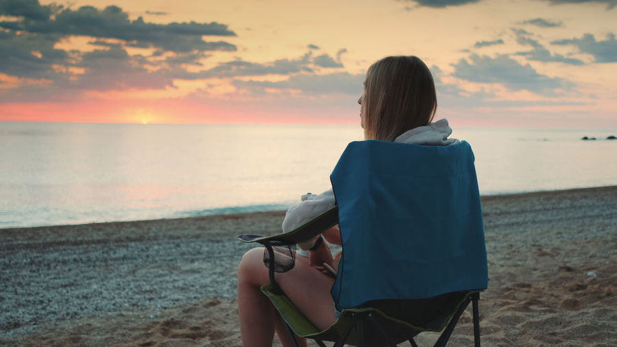 Rear view of woman sitting on beach during sunset