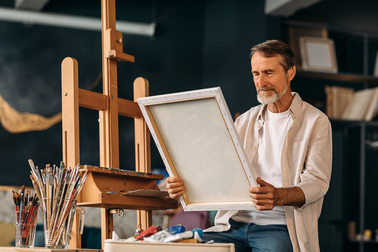 Senior man holding painting