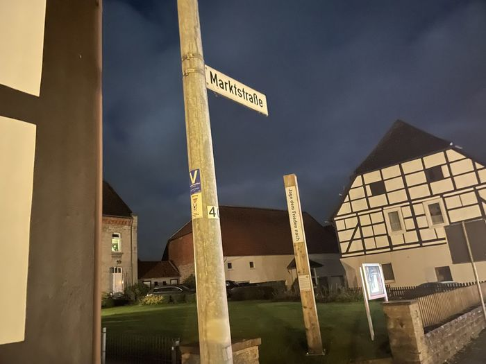 Low angle view of road sign by building against sky