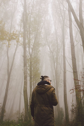 Man standing amidst trees during foggy weather